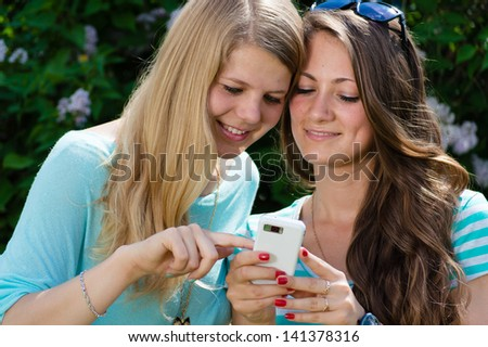 Two happy teen girl friends looking on mobile phone while sitting on green lawn on summer day - stock photo