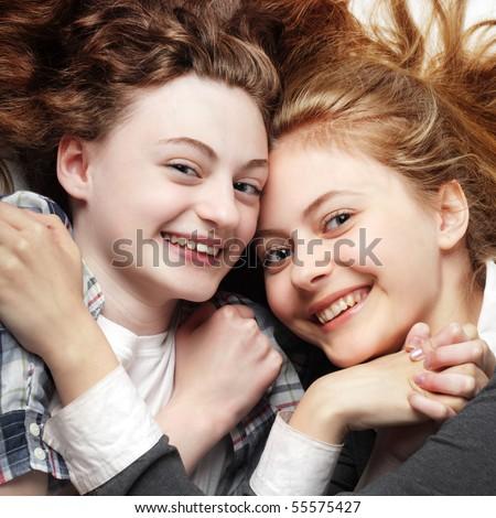 two happy teen laying on floor - stock photo