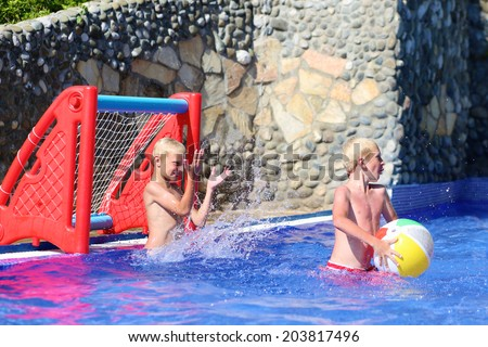 Two happy teenage boys, sportive twin brothers, having fun together playing waterpolo with colorful inflatable ball in outdoors swimming pool in aquapark during summer sea vacation in tropical resort - stock photo