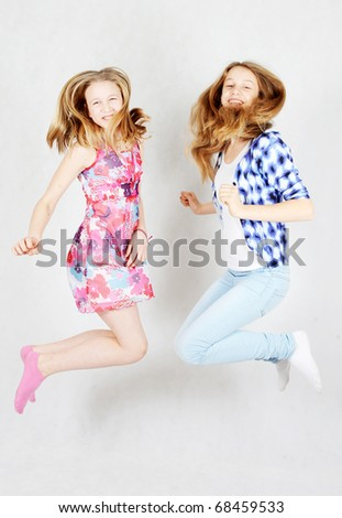 Two happy teenage girls jumping at once - stock photo