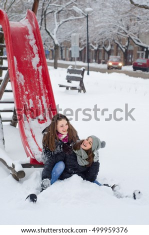 Two happy teenage girls playing in the snow on beautiful winter day.