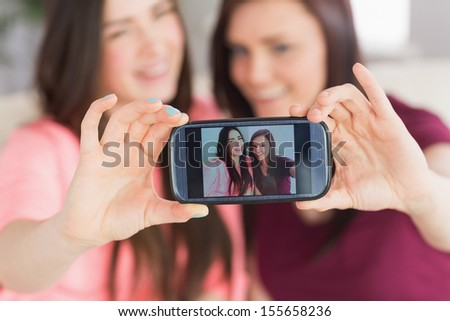 Two happy teenage girls sitting on a sofa taking a photo of themselves with a mobile phone in a living room - stock photo