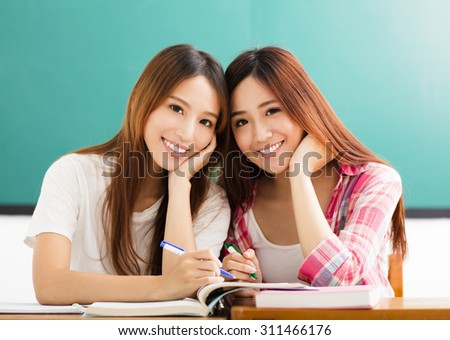 Two  happy teenage students girls in classroom - stock photo