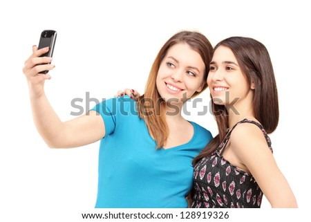 Two happy teenagers taking pictures of themselves with a cell phone isolated on white background - stock photo