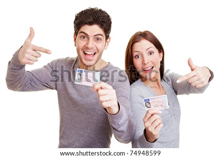 Two happy teens pointing to their European driving license - stock photo