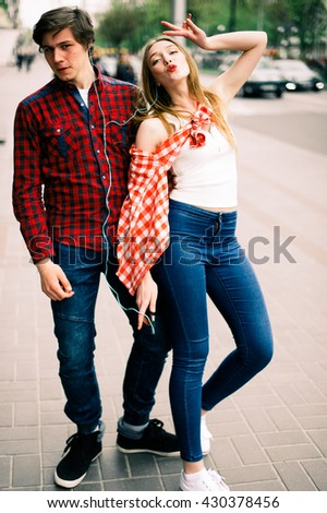 Two happy trendy teenage friends walking in the city, talking each other and smiling. Lifestyle, friendship and urban life concepts. - stock photo