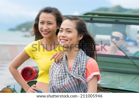 Two happy Vietnamese girls standing in front of off-road vehicle - stock photo