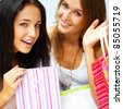 Two happy women at a shopping center with bags. Seasonal preparty shopping boom. - stock photo