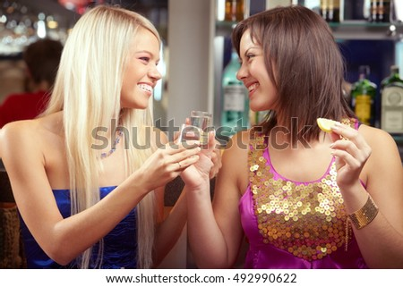 Two happy women drinking alcohol and laughing