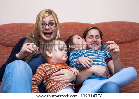 Two happy women playing with children at home - stock photo