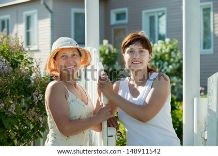 Two happy women talking near fence wicket
