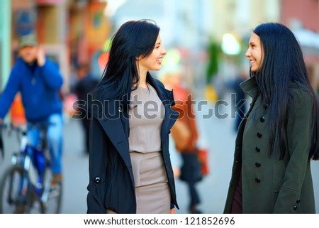 two happy women talking on crowded city street - stock photo