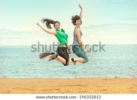 Two happy women with broom jumping on the beach  - stock photo