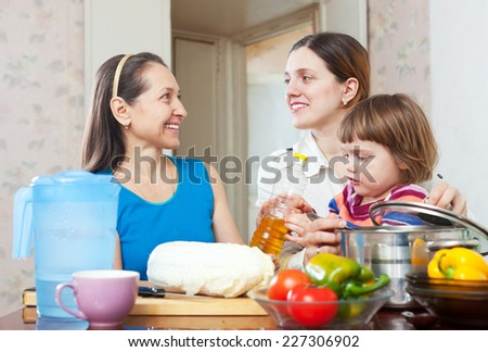 Two happy women with child cook vegetables in kitchen at home - stock photo