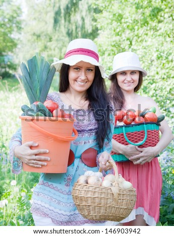 Two happy women with  harvested vegetables in garden - stock photo