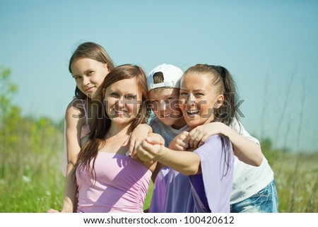 Two happy  women with teens sitting at nature - stock photo