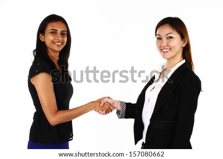 Two happy young Asian business women shaking hands; on a white background - stock photo