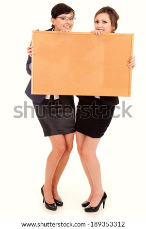two happy young business women standing and holding the cork board, white background - stock photo