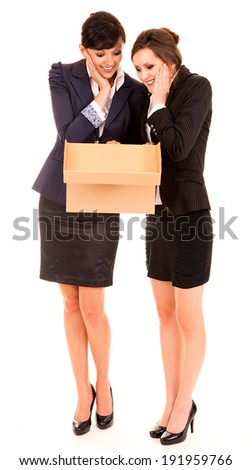 two happy young business women with carton box, standing and smiling, white background - stock photo