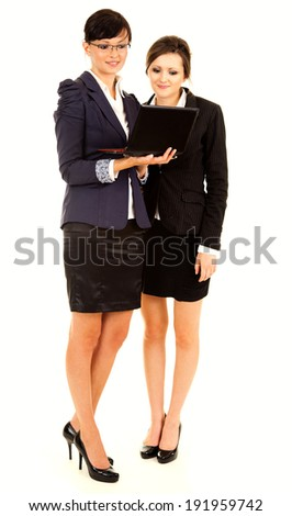 two happy young business women with laptop, standing and smiling, full lenght, white background