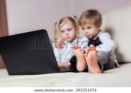 two happy young children: white-skinned boy blond girl sitting with a black cat and a laptop (brother and sister) on a white sofa watching cartoons in the computer, people blurred, legs in Focus - stock photo