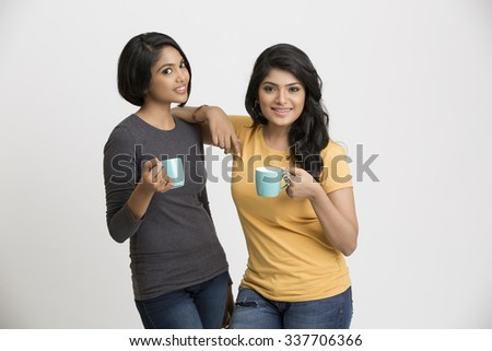 Two happy young female friends posing with coffee cups on white background. - stock photo