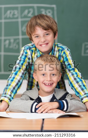 Two happy young friends in school posing with the one boy leaning over the other seated at his desk both grinning happily at the camera - stock photo