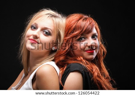 two happy young girlfriends blonde and red-hair black background - stock photo