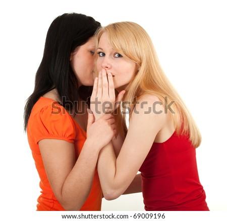two happy young girlfriends talking, gossips in secret - stock photo