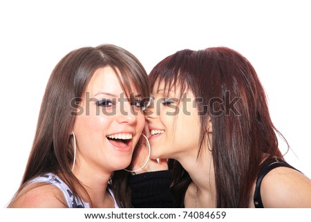 two happy young girlfriends talking over white - focused on the right girl