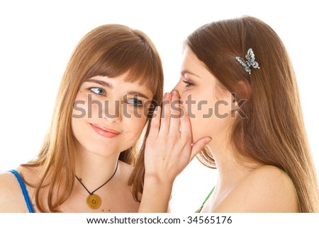 Two happy young girlfriends telling secrets. Isolated on white background