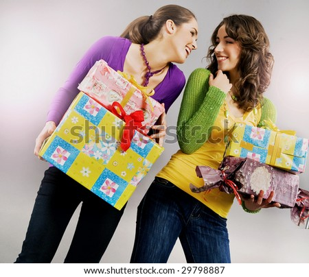 Two happy young girls holding presents - stock photo