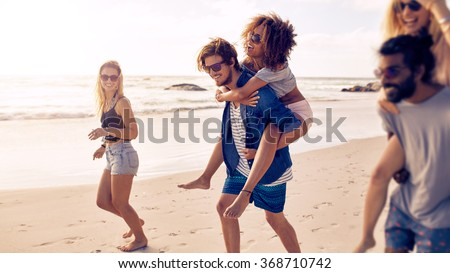Two happy young men giving their girlfriends piggyback rides at the beach. Group of friends enjoying beach holidays. - stock photo