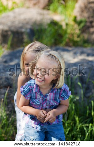 Two happy young sisters playing together in a green grass - stock photo