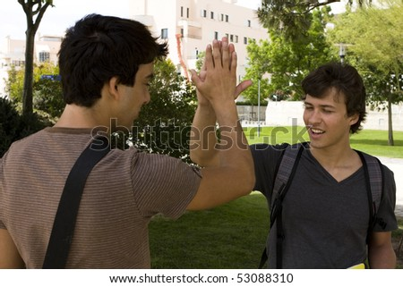 Two happy young student giving a handshake (selective focus) - stock photo