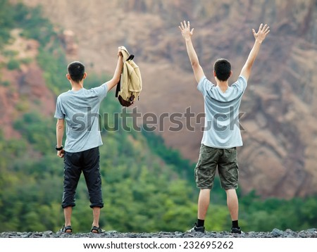 Two happy young tourist men standing on rocky cliff and enjoying nature - stock photo