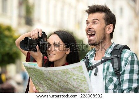 Two happy young tourists with backpacks, touristic map and camera. Sightseeing City. - stock photo