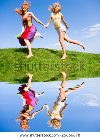 Two happy young women are runing in a field - stock photo