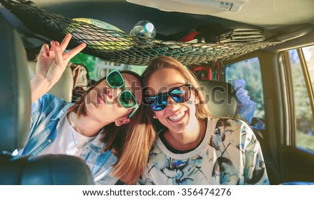 Two happy young women friends with sunglasses laughing and having fun inside of car in a road trip adventure. Female friendship and leisure time concept. - stock photo