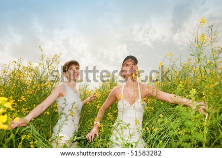 Two happy young women in field - stock photo