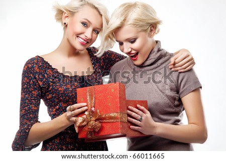 Two happy young women posing with a christmas gift - stock photo