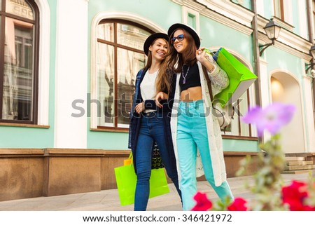 Two happy young women shopping and carry bags