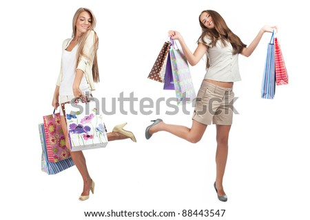 Two happy young women with colorful shopping bags dancing and smiling. Isolated on white background