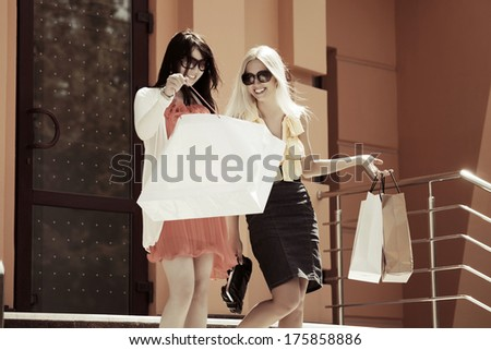 Two happy young women with shopping bags  - stock photo