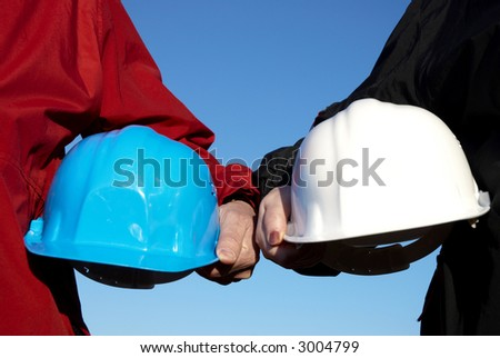 two hard-hats (blue and white color) focus on hand of man - stock photo