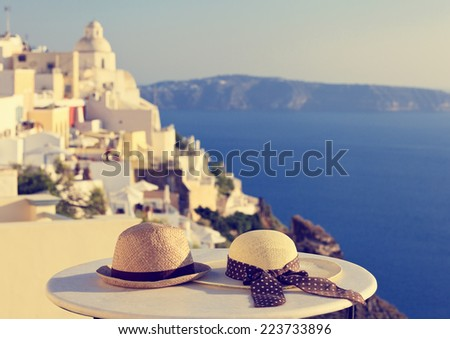 two hats on Santorini island, image of honeymoon and summer vacation - stock photo
