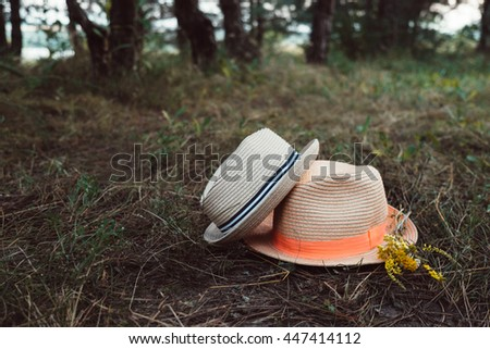 Two hats with wild flowers on grass in the forest in summer. Wilderness nature background with hats couple. Outdoor family travel and adventure, summer holidays. Hiking and exploring nature. - stock photo