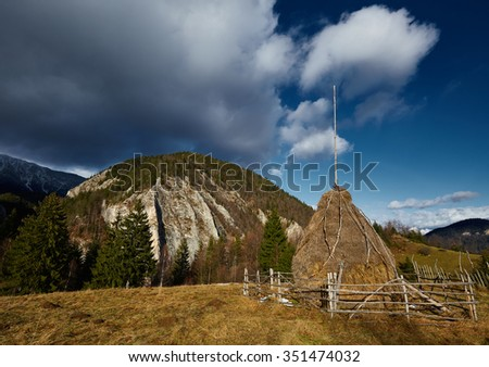 Two hay ricks with mountains in background - stock photo