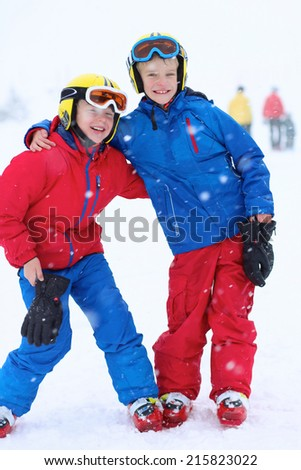 Two healthy happy school  boys, twin brothers in colorful snowsuits, having fun skiing in alpine mountains during snowy winter vacation - stock photo