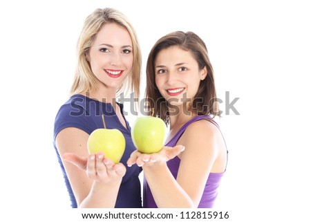 Two healthy women with apples Two happy healthy women standing with their palms extended holding juicy ripe apples in a diet and fitness concept - stock photo